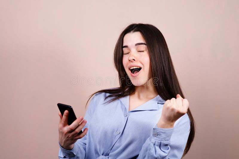 Happy woman winning online. Young excited lady using smart phone. Achievement, celebration, success concept royalty free stock photos