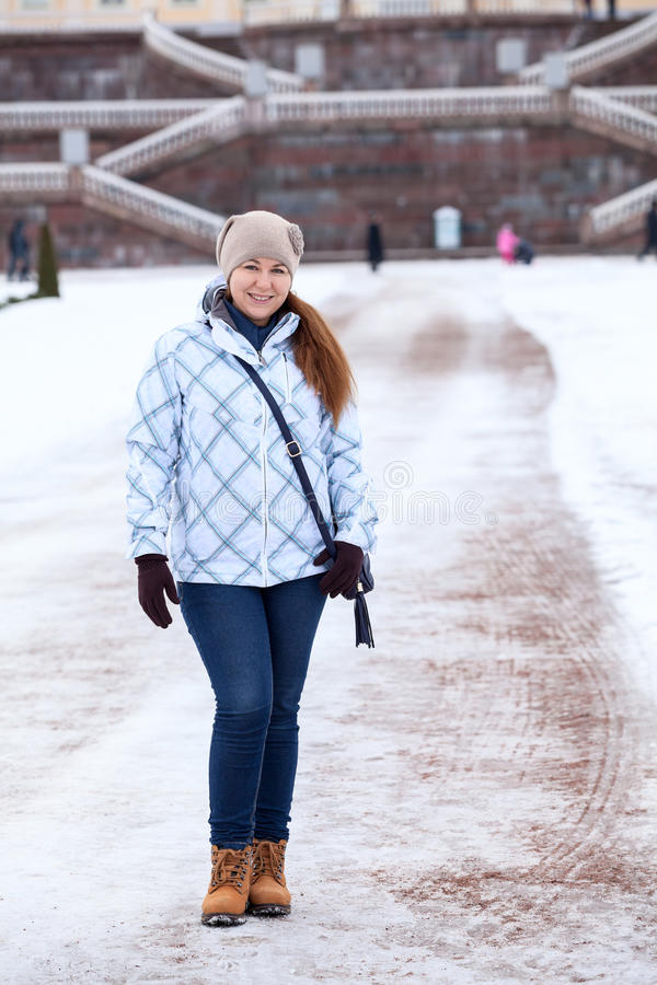 Happy woman in winter clothes standing in front of the Palace staircase. Woman in winter clothes standing in front of the Palace staircase royalty free stock photos