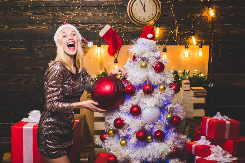 Happy woman. Winter holidays and people concept. Blonde Santa woman holding gift at vintage wooden wall. Beautiful Woman royalty free stock photo