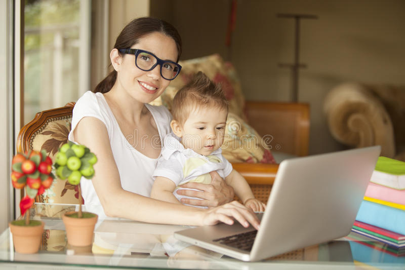Happy woman working with baby. Happy women working with baby at home royalty free stock photo