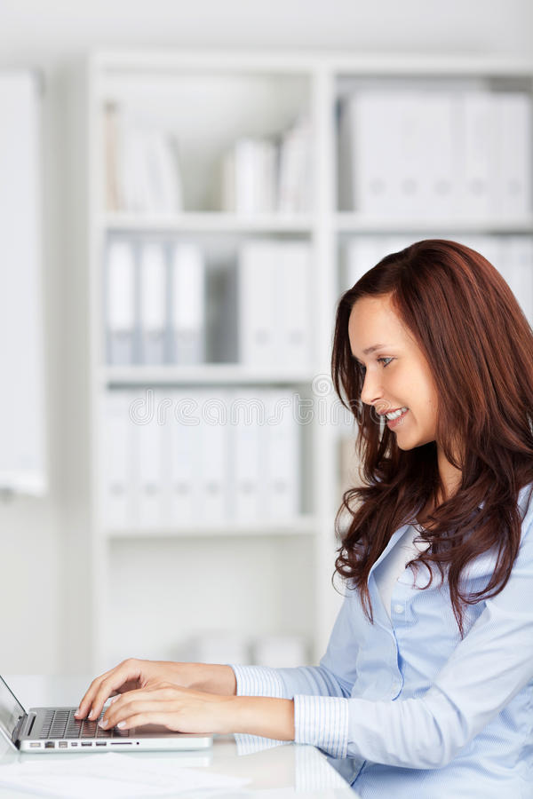 Happy woman working at her laptop stock photos