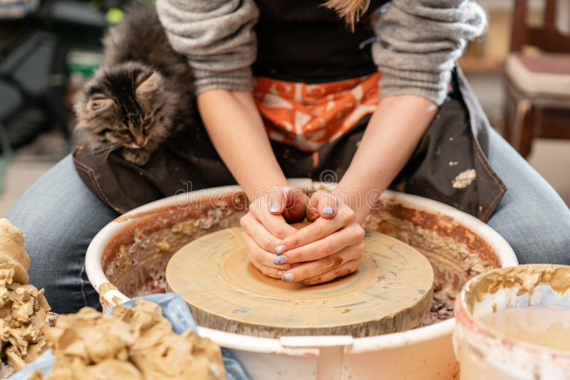 Happy woman working on potter wheel in pottery workshop. Family business shop sculpts pot from clay view top. Happy woman working on potter wheel in pottery royalty free stock photography