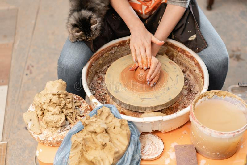 Happy woman working on potter wheel in pottery workshop. Family business shop sculpts pot from clay view top. Happy woman working on potter wheel in pottery royalty free stock images