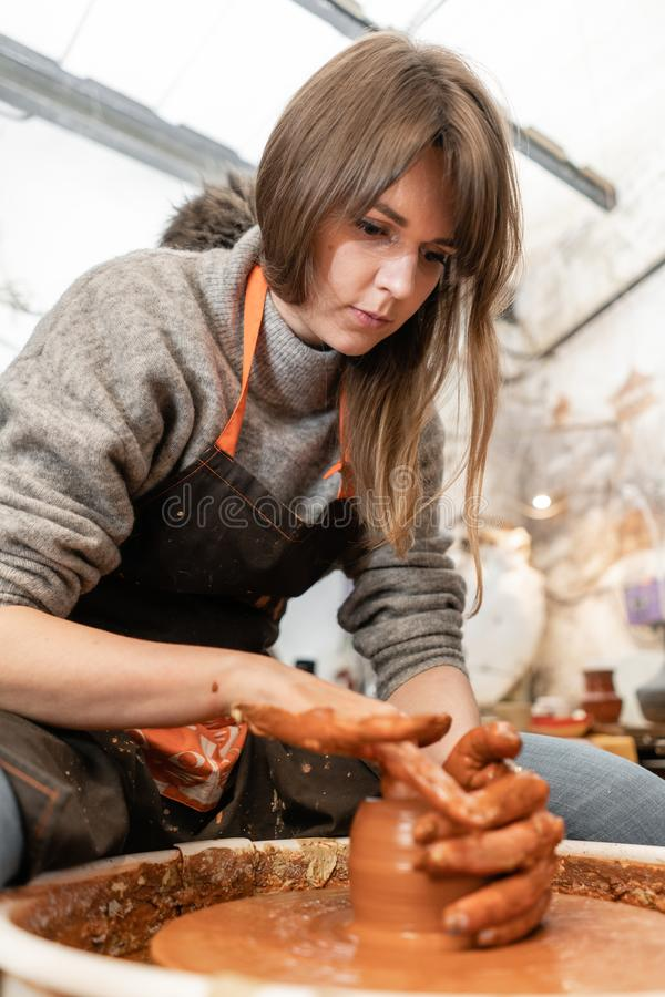 Happy woman working on potter wheel in pottery workshop. Family business shop sculpts pot from clay view top. Happy woman working on potter wheel in pottery stock photo