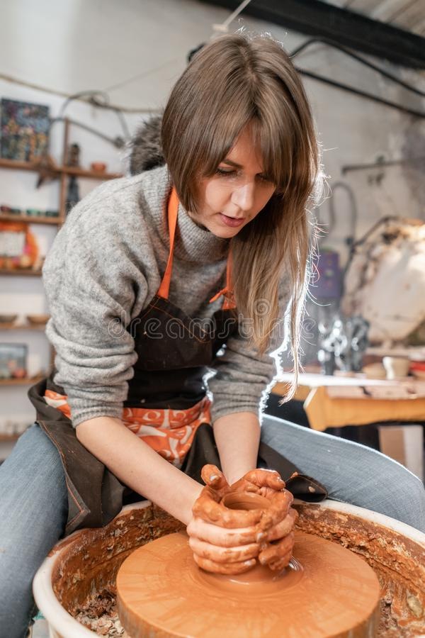 Happy woman working on potter wheel in pottery workshop. Family business shop sculpts pot from clay view top. Happy woman working on potter wheel in pottery stock images