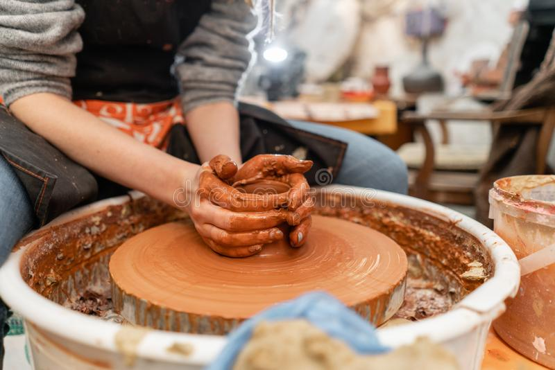 Craftsman hands making pottery bowl. Woman working on potter wheel . Family business shop sculpts pot from clay view top. Happy woman working on potter wheel in royalty free stock photos
