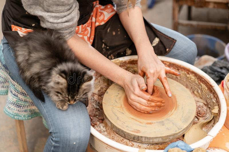 Happy woman working on potter wheel in pottery workshop. Family business shop sculpts pot from clay view top. Happy woman working on potter wheel in pottery royalty free stock image