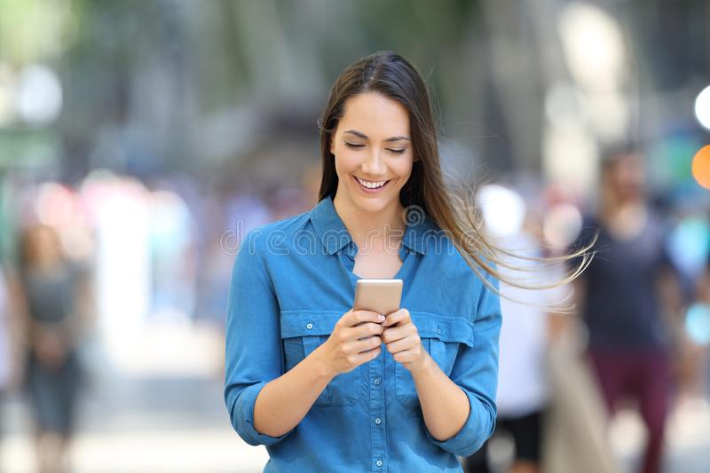 Happy woman writing message in a smart phone on the street. Front view of a happy woman writing message in a smart phone on the street royalty free stock photos