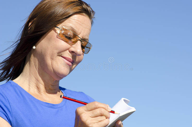 Happy woman writing a note stock photos