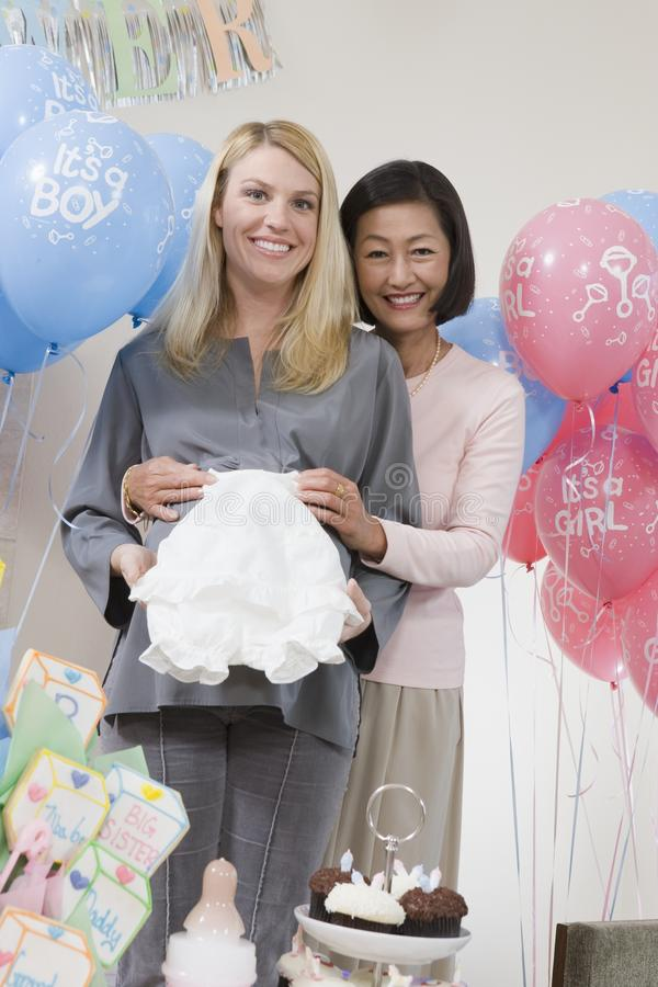 Happy Women With Baby Clothes At A Baby Shower. Portrait of mature women holding baby clothes on pregnant woman's belly royalty free stock photo