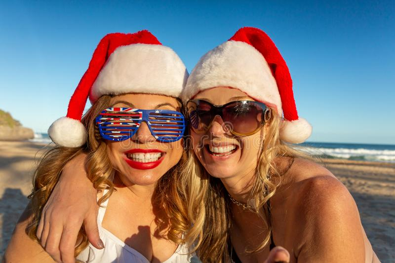 Happy women on the beach at Christmas stock photo