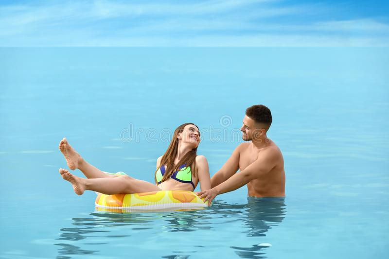 Happy woman in bikini floating on inflatable ring and her boyfriend. Lovely couple royalty free stock photography