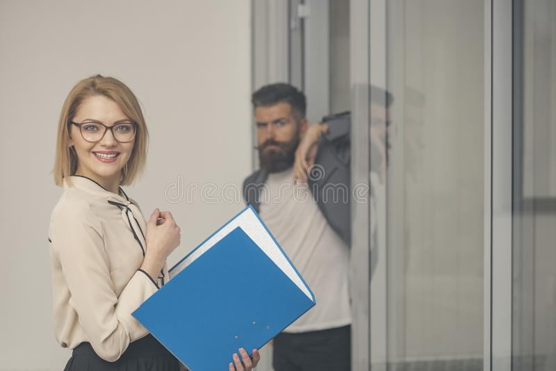 Happy woman with blurred man on background. Businesswoman in glasses hold binder in office. accountant smile with stock image