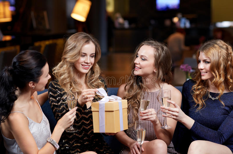 Happy women with champagne and gift at night club. Celebration, friends, bachelorette party, birthday and holidays concept - happy women with champagne glasses royalty free stock photo