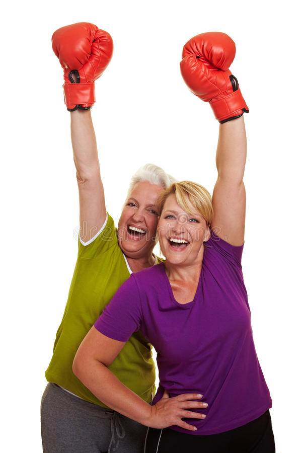 Happy women cheering with red. Two happy women cheering with red boxing gloves royalty free stock photo