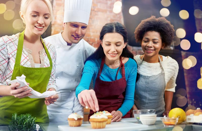 Happy women and chef cook baking in kitchen. Cooking class, culinary, bakery, food and people concept - happy group of women and male chef cook baking in kitchen stock image