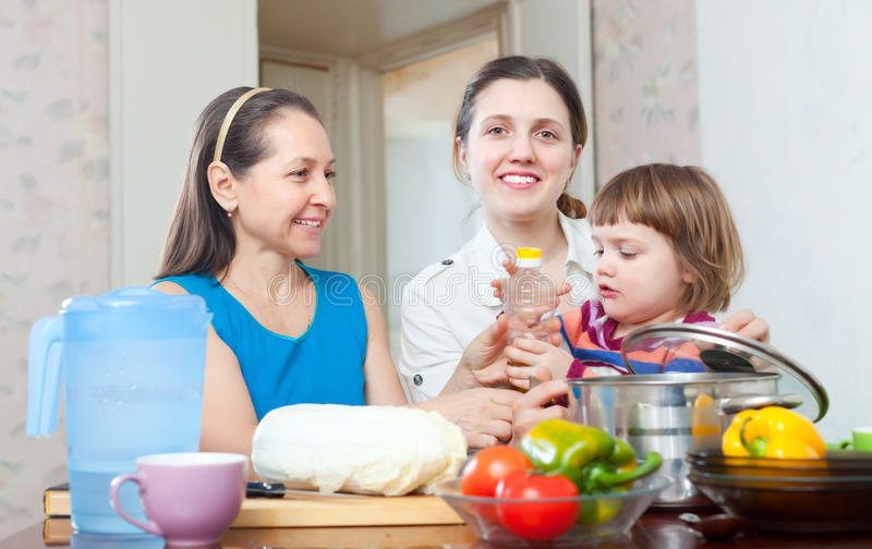 Happy women with child in kitchen. Happy women with child cook vegetables in kitchen at home stock images