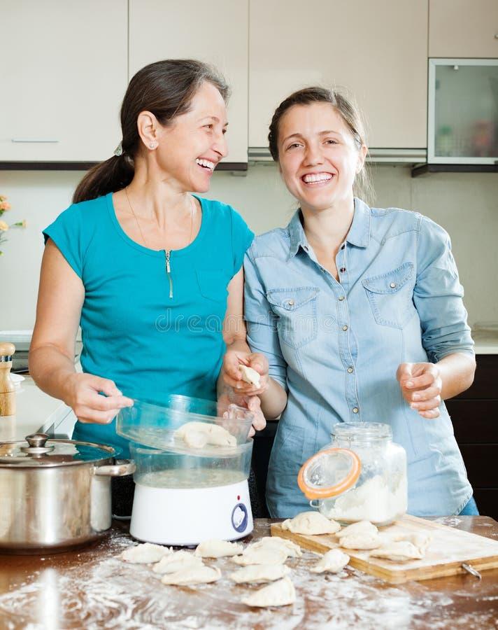 Happy women cooking dumplings royalty free stock images