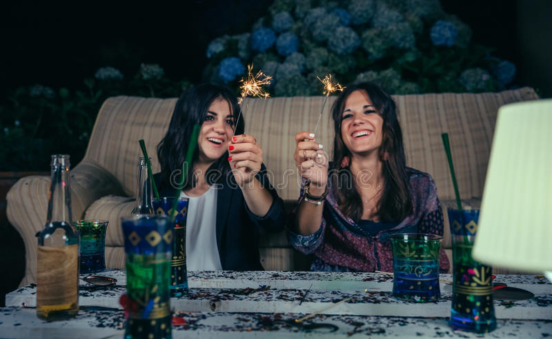 Happy women couple holding sparklers in a party. Portrait of happy young women friends laughing and holding sparklers in a outdoors night party. Selective focus stock photos