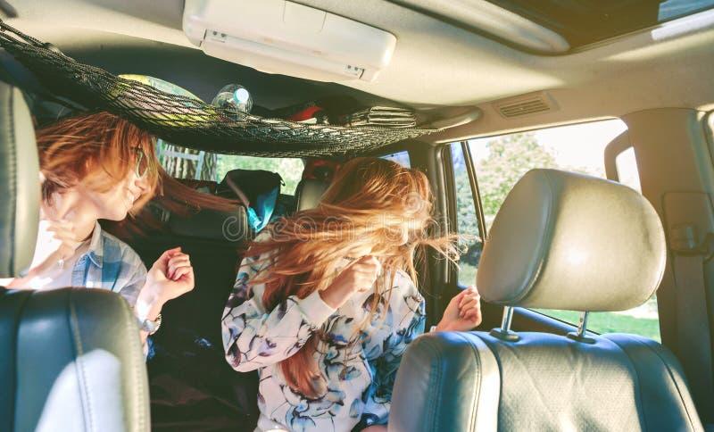 Happy women dancing and having fun inside of car stock photography