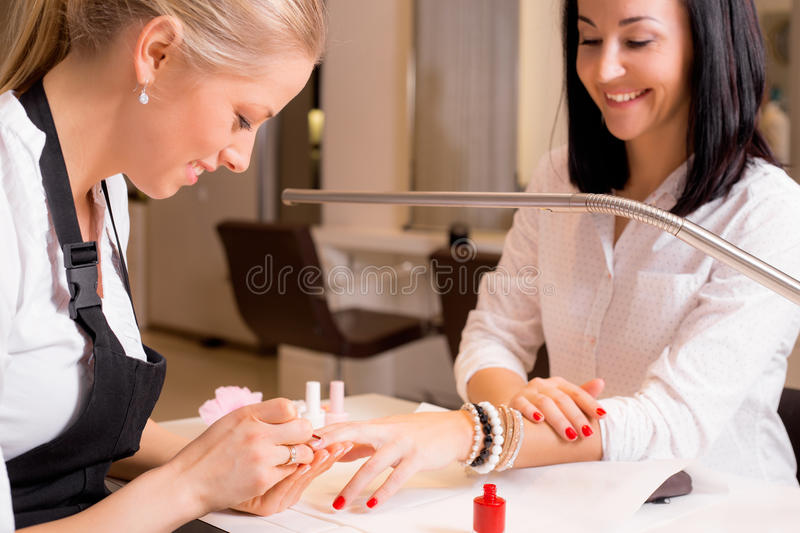 Happy women doing manicure. At the saloon royalty free stock photography
