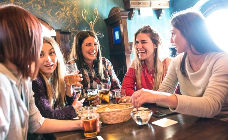 Happy women drinking beer at brewery restaurant - Female friendship concept with young girlfriends enjoying time together stock image