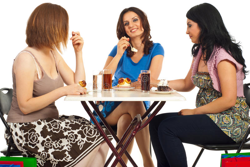 Happy women eating cakes at table. Three women having a meeting after shopping and eating cakes at table stock photos
