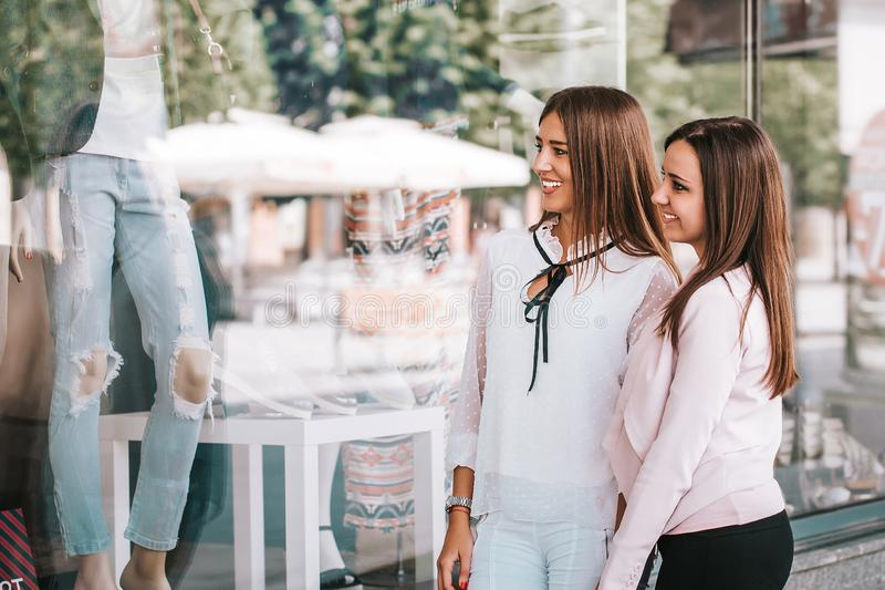 Happy women enjoy shopping while looking shop windows together royalty free stock photography