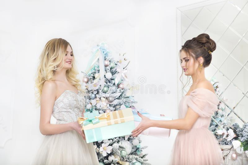 Women holding gifts over by the Christmas tree royalty free stock images