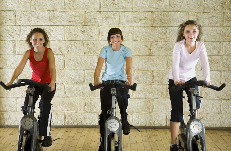 Happy women on exercise bikes royalty free stock photos
