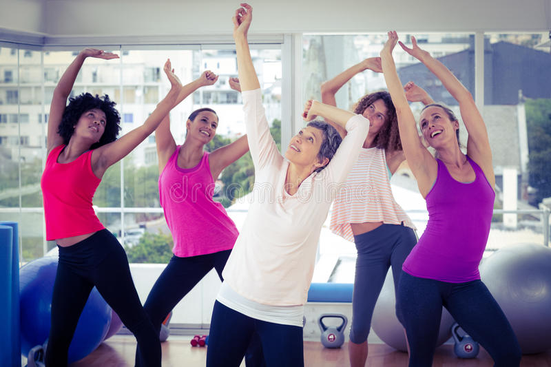 Happy women exercising with arms raised while looking up. In fitness studio royalty free stock photography