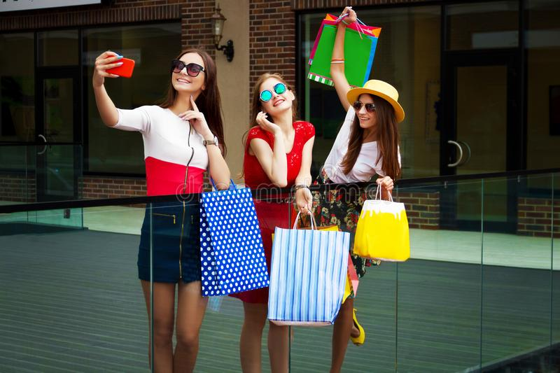 Happy women friends customers with shopping bags doing selfie royalty free stock photography