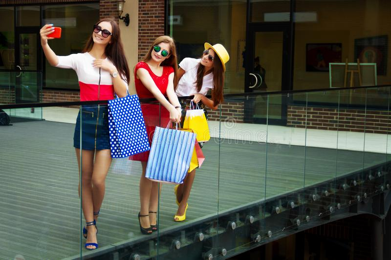 Happy women friends customers with shopping bags doing selfie. Pretty happy bright women female girls friends in colorful dresses, hats and high heels with stock photo