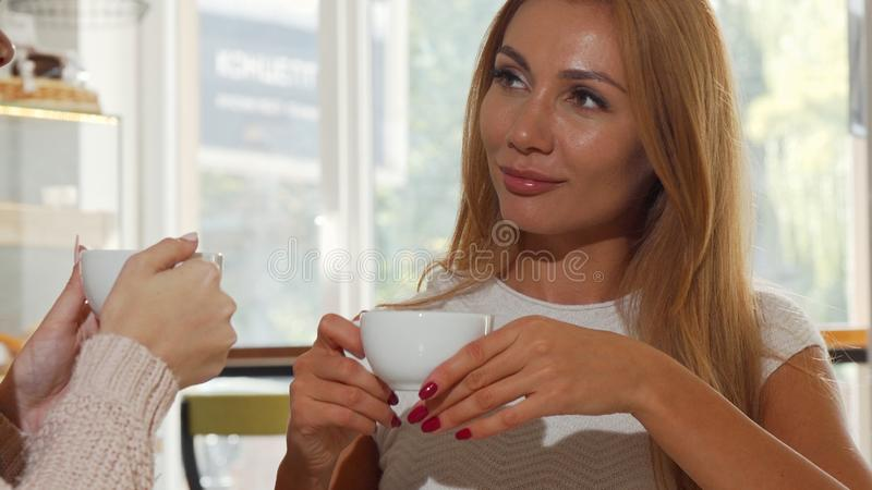Happy women friends talking over a cup of coffee at cozy bakery shop royalty free stock photo