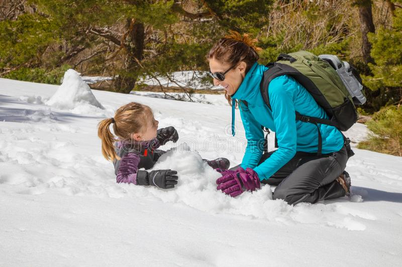 Mother and little girl laughing on the snow stock photos