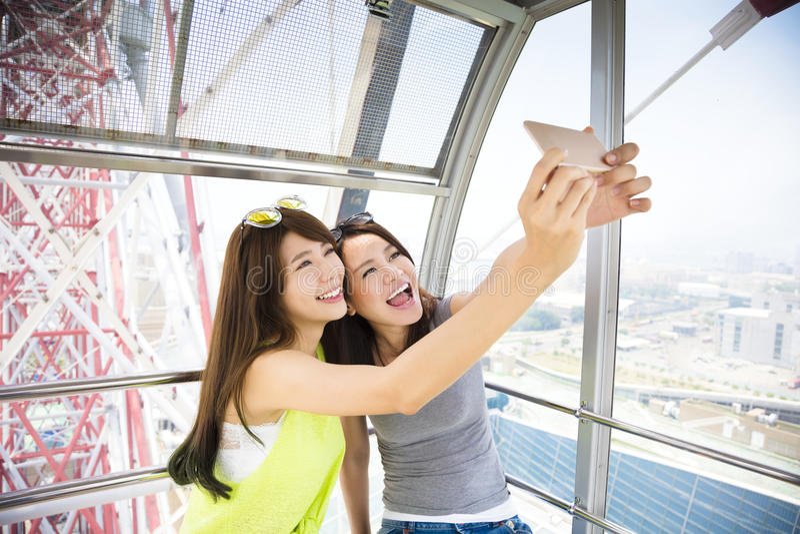 Happy women girlfriends taking a selfie in ferris wheel royalty free stock image
