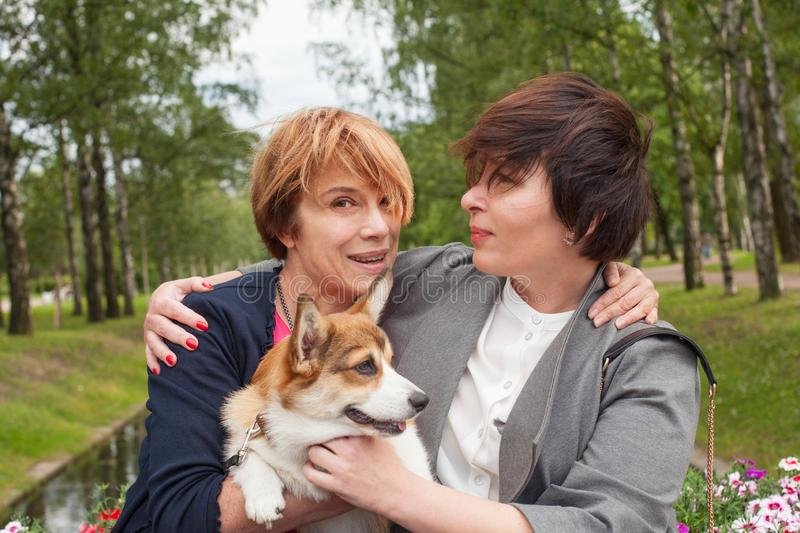 Happy women having fun with dog pet in summer park. Lifestyle portrait royalty free stock photo