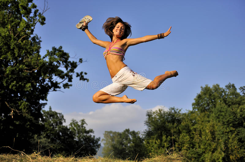 Happy women jumping on summer time. Happy woman jumping on summer time. She is wearing short white pants and bikini. She is holding flip-flops in her hand. she stock photos