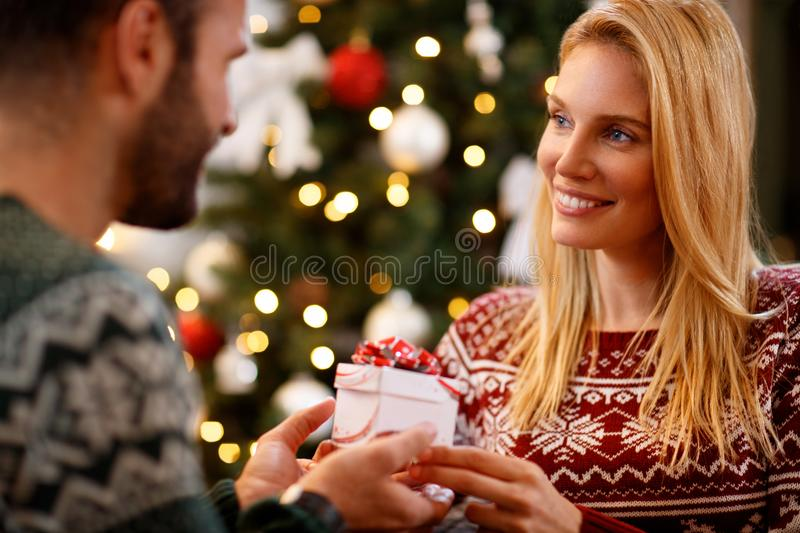 Woman giving Christmas present to her husband royalty free stock image