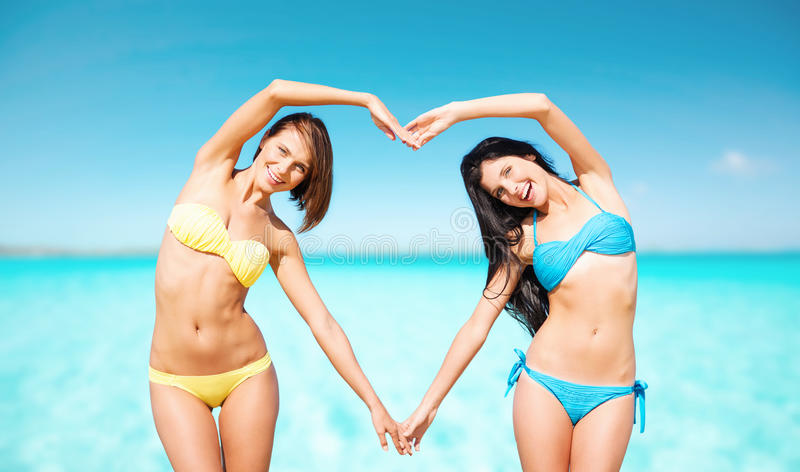 Happy women making heart shape on summer beach. Summer holidays, travel, people, love and vacation concept - happy young women in bikinis making heart shape with stock image