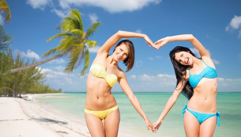 Happy women making heart shape on summer beach royalty free stock photo