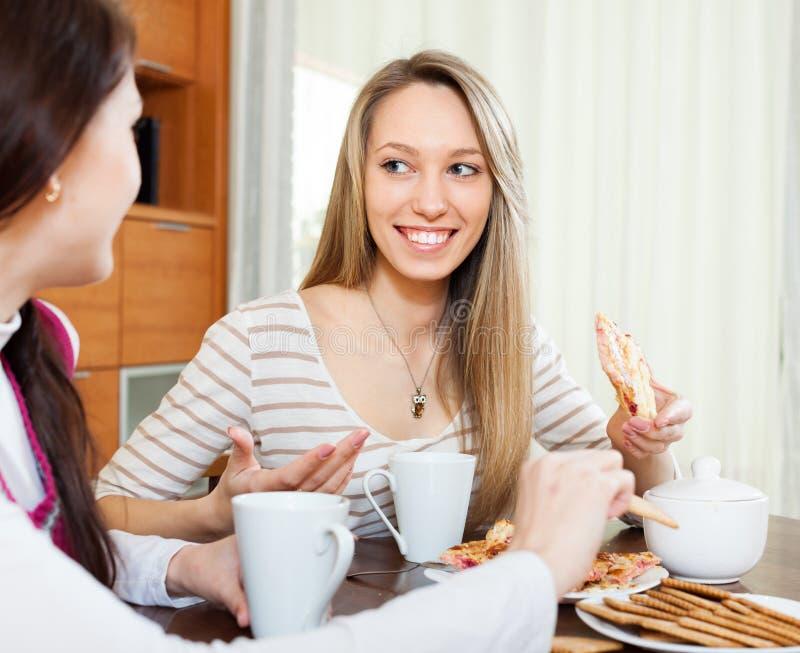 Happy women over tea table in kitchen stock image