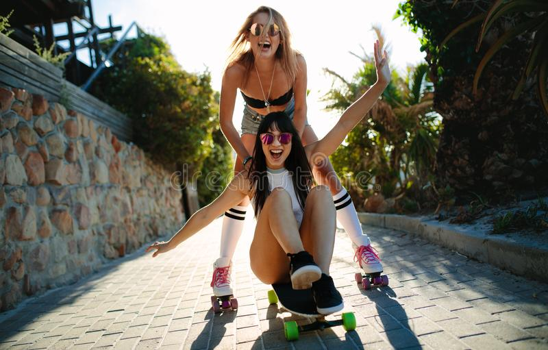 Beautiful girls having fun on a skateboard stock images
