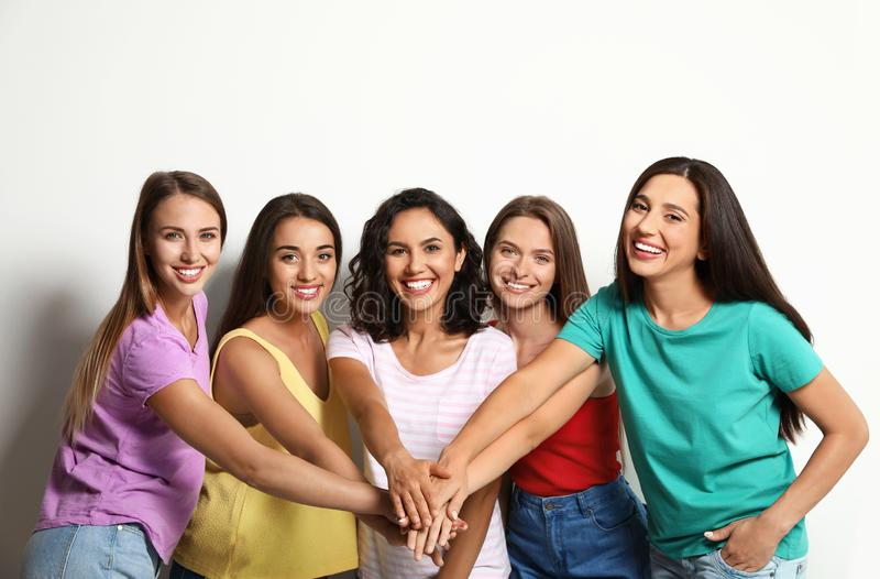 Happy women putting hands together. Girl power concept stock images