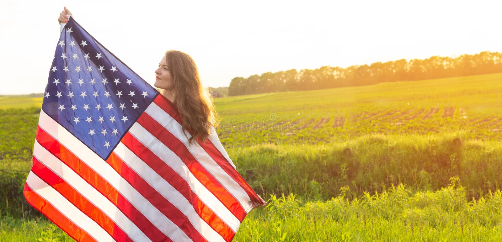 Happy women running in the field with American flag USA celebrate 4th of July royalty free stock photography