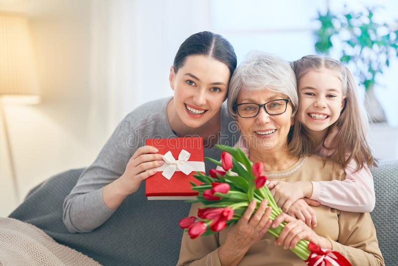 Happy women`s day. ! Child daughter is congratulating mom and granny giving them flowers tulips. Grandma, mum and girl smiling and hugging. Family holiday and stock photo