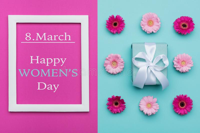 Happy Women`s Day Pastel Candy Colours Background. Floral womens day flat lay with beautifully wrapped present. royalty free stock photos