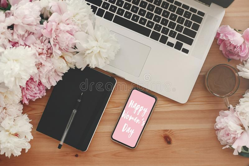 Happy Women`s Day text sign on phone screen at laptop, notebook, coffee and peonies on rustic wooden table flat lay. Girl Power. Stylish floral greeting card stock image