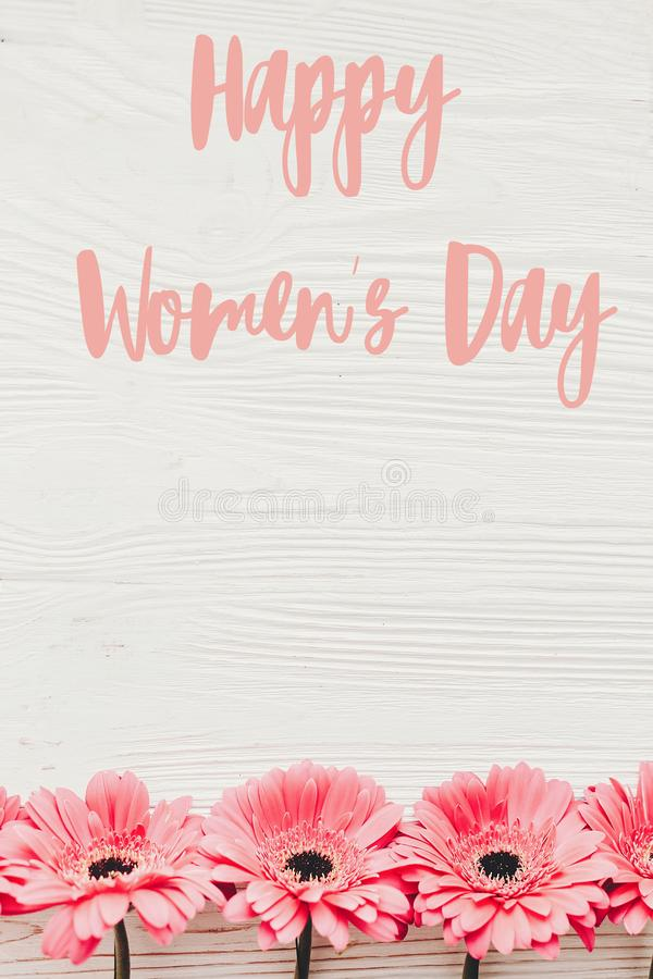 Happy Women`s Day text sign at pink gerbera on white wooden background, flat lay. Floral greeting card. Girl Power. Internationa. L womens day, 8 march stock images