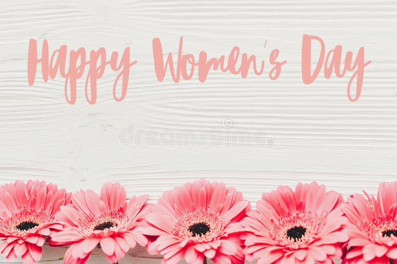 Happy Women`s Day text sign at pink gerbera on white wooden background, flat lay. Floral greeting card. Girl Power. Internationa. L womens day, 8 march royalty free stock photo